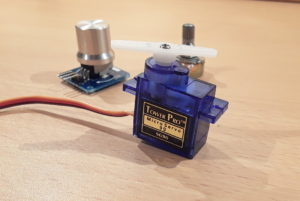 The SG90 micro servo motor. In the background is a rotary angle sensor module and a potentiometer. Both can be used to control the servo motor.